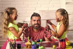 Τα παιδιά σύρουν έναν μπαμπά Τα κορίτσια που επισύρουν την προσοχή στο άτομο αντιμετωπίζουν το δέρμα με τα ζωηρόχρωμα χρώματα στοκ εικόνα με δικαίωμα ελεύθερης χρήσης