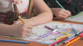 Τα παιδιά σύρουν τις εικόνες χρησιμοποιώντας τα μολύβια στα λευκώματα απόθεμα βίντεο