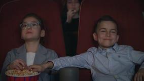 Τα παιδιά τρώνε popcorn στον κινηματογράφο Προσχολικά παιδιά που προσέχουν τον κινηματογράφο στον κινηματογράφο απόθεμα βίντεο