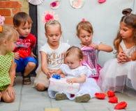 Τα παιδιά φαίνονται κιβώτια με τα δώρα Διακοπές παιδιών Στοκ Εικόνα