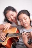 Τα παιδιά φορούν ένα άσπρο ακουστικό ακούοντας τη μουσική στοκ εικόνα με δικαίωμα ελεύθερης χρήσης