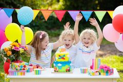 Τα παιδιά φυσούν τα κεριά στο κέικ γενεθλίων Κόμμα παιδιών στοκ εικόνα με δικαίωμα ελεύθερης χρήσης