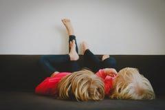 Τα παιδιά χαλαρώνουν στο σπίτι - εγχώριες άνεση και τεμπελιά στοκ φωτογραφίες