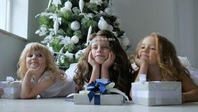 Τα παιδιά Χριστουγέννων βρίσκονται στο πάτωμα με την κινηματογράφηση σε πρώτο πλάνο κιβωτίων δώρων στο υπόβαθρο του διακοσμημένου απόθεμα βίντεο