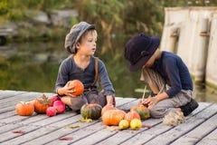 Τα παιδιά χρωματίζουν τις μικρές κολοκύθες αποκριών Στοκ Φωτογραφίες