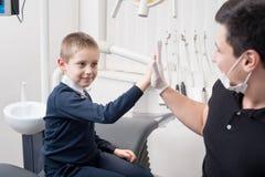 Τα παιδιατρικά χέρια κουνημάτων οδοντιάτρων με το νέο αγόρι, συγχαίρουν τον ασθενή για μια επιτυχή θεραπεία στο οδοντικό γραφείο Στοκ Εικόνα
