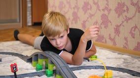 Τα παιδικά παιχνίδια με το σιδηρόδρομο παιδιών ` s Ένας έφηβος στο χώρο για παιχνίδη, που παίζει με ένα σύνολο κατασκευής, συλλογ φιλμ μικρού μήκους