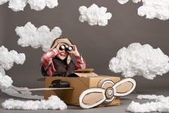 Τα παιχνίδια αγοριών σε ένα αεροπλάνο φιαγμένο από κουτί από χαρτόνι και όνειρα να γίνουν πειραματικά, καλύπτουν cottonwool σε έν Στοκ Εικόνα