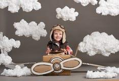 Τα παιχνίδια αγοριών σε ένα αεροπλάνο φιαγμένο από κουτί από χαρτόνι και όνειρα να γίνουν πειραματικά, καλύπτουν cottonwool σε έν Στοκ Φωτογραφία
