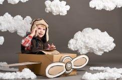 Τα παιχνίδια αγοριών σε ένα αεροπλάνο φιαγμένο από κουτί από χαρτόνι και όνειρα να γίνουν πειραματικά, καλύπτουν cottonwool σε έν Στοκ εικόνες με δικαίωμα ελεύθερης χρήσης