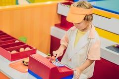 Τα παιχνίδια αγοριών στον πωλητή των burgers στοκ εικόνα