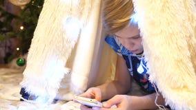 Τα παιχνίδια εφήβων στο smartphone στο δωμάτιο των παιδιών σε μια σκηνή με ένα φως Χριστουγέννων παιδική ηλικία ευτυχής στοκ εικόνα με δικαίωμα ελεύθερης χρήσης