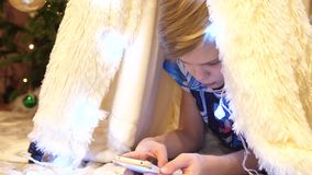 Τα παιχνίδια εφήβων στο smartphone στο δωμάτιο των παιδιών σε μια σκηνή με ένα φως Χριστουγέννων παιδική ηλικία ευτυχής απόθεμα βίντεο
