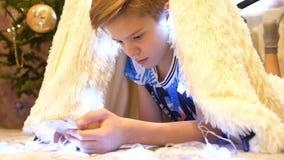 Τα παιχνίδια εφήβων στο smartphone στο δωμάτιο των παιδιών σε μια σκηνή με ένα φως Χριστουγέννων παιδική ηλικία ευτυχής στοκ εικόνες