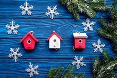 Τα παιχνίδια και snowflakes σπιτιών για το νέο εορτασμό έτους με το δέντρο γουνών διακλαδίζονται στην μπλε ξύλινη κορυφή υποβάθρο Στοκ Φωτογραφία