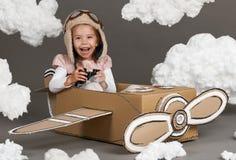 Τα παιχνίδια κοριτσιών παιδιών σε ένα αεροπλάνο φιαγμένο από κουτί από χαρτόνι και όνειρα να γίνουν πειραματικά, καλύπτουν cotton Στοκ Εικόνες