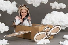 Τα παιχνίδια κοριτσιών παιδιών σε ένα αεροπλάνο φιαγμένο από κουτί από χαρτόνι και όνειρα να γίνουν πειραματικά, καλύπτουν cotton Στοκ εικόνες με δικαίωμα ελεύθερης χρήσης