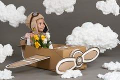 Τα παιχνίδια κοριτσιών παιδιών σε ένα αεροπλάνο φιαγμένο από κουτί από χαρτόνι και όνειρα να γίνουν πειραματικά, καλύπτουν cotton Στοκ φωτογραφία με δικαίωμα ελεύθερης χρήσης