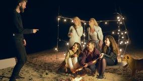 Τα παιχνίδια νεολαίας, φίλοι παίζουν στην ψυχαγωγία διασκέδασης από την πυρά προσκόπων στην άμμο στις διακοπές απόθεμα βίντεο