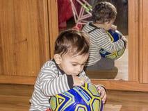Τα παιχνίδια παιδιών με μια σφαίρα Συναισθηματικό πορτρέτο ενός 1χρονου παιδιού στοκ εικόνες