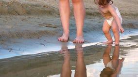 Τα παιχνίδια παιδιών στις όχθεις του ποταμού, παίρνουν την υγρή άμμο με το χέρι του mom με τον περίπατο παιδιών στην παραλία κατά απόθεμα βίντεο