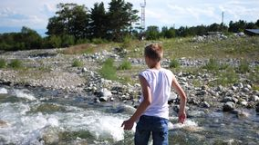Τα παιχνίδια τύπων στην όχθη ποταμού, ρίχνουν τις πέτρες στο νερό Κρύος ποταμός βουνών Υπαίθρια αναψυχή απόθεμα βίντεο