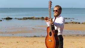 τα παιχνίδια κιθαριστών κάνουν τα τεχνάσματα με την κιθάρα ενάντια στην παραλία θάλασσας απόθεμα βίντεο