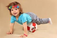 Τα παιχνίδια μικρών κοριτσιών με μια σφαίρα στοκ εικόνα