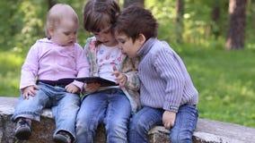 Τα παιχνίδια μικρών κοριτσιών με το PC ταμπλετών, το αγόρι και το μικρό κορίτσι εξετάζουν το απόθεμα βίντεο