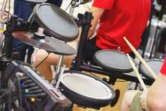 Τα παιχνίδια μουσικών σε ένα ηλεκτρονικό σύνολο τυμπάνων Μουσικές αποδόσεις στιγμής Στοκ εικόνα με δικαίωμα ελεύθερης χρήσης