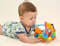 Τα παιχνίδια μωρών με ένα παιχνίδι, που βρίσκεται σε ένα στομάχι Στοκ φωτογραφία με δικαίωμα ελεύθερης χρήσης