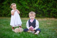 Τα παιδάκια με ένα κουνέλι λαγουδάκι έχουν ένα Πάσχα στο πράσινο υπόβαθρο χλόης Στοκ Φωτογραφία