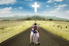 Τα παιδιά αγκαλιάζουν τον πατέρα τους με ένα σημάδι του σταυρού στον ουρανό Στοκ Εικόνες