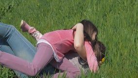 Τα παιδιά αγκαλιάζουν mom στο πάρκο Τα κορίτσια ρίχνουν τη μητέρα στην πράσινη χλόη Οικογένεια στο πάρκο σε ένα ηλιόλουστο απόγευ απόθεμα βίντεο