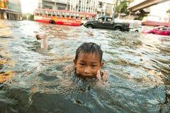 Τα παιδιά απολαμβάνουν τις πλημμυρισμένες οδούς που λούζουν Στοκ εικόνες με δικαίωμα ελεύθερης χρήσης