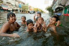 Τα παιδιά απολαμβάνουν τις πλημμυρισμένες οδούς που λούζουν Στοκ φωτογραφία με δικαίωμα ελεύθερης χρήσης