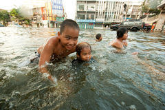 Τα παιδιά απολαμβάνουν τις πλημμυρισμένες οδούς που λούζουν Στοκ Φωτογραφίες