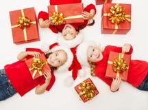 Τα παιδιά αρωγών Χριστουγέννων με το κόκκινο παρουσιάζουν το κιβώτιο δώρων  στοκ εικόνες με δικαίωμα ελεύθερης χρήσης