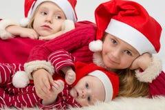 Τα παιδιά βρίσκονται στα καπέλα Άγιου Βασίλη Στοκ Εικόνα