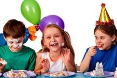 Τα παιδιά γενεθλίων γιορτάζουν το κόμμα και κατανάλωση του κέικ στο πιάτο από κοινού Στοκ Εικόνες
