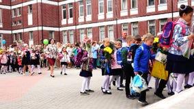 Τα παιδιά γιορτάζουν την ημέρα της γνώσης με τα λουλούδια και τα μπαλόνια απόθεμα βίντεο