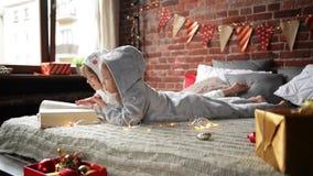 Τα παιδιά είναι ντυμένα στις θερμές πυτζάμες Χριστουγέννων διαβάζοντας μια συνεδρίαση βιβλίων ενδιαφέροντος στο κρεβάτι, backgrau απόθεμα βίντεο