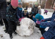 Τα παιδιά διαμορφώνουν και χρωματίζοντας το χιονάνθρωπο Στοκ εικόνα με δικαίωμα ελεύθερης χρήσης