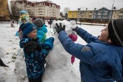 Τα παιδιά διαμορφώνουν και χρωματίζοντας το χιονάνθρωπο Στοκ Φωτογραφίες