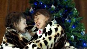 Τα παιδιά κάθονται κάτω από μια κουβέρτα κοντά στο χριστουγεννιάτικο δέντρο Δύο μικρά κορίτσια καλύπτονται με ένα επισημασμένο κά απόθεμα βίντεο