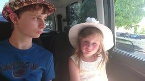 Τα παιδιά κάθονται στο αυτοκίνητο έτοιμος να πάει στις θερινές διακοπές θερινό παιχνίδι διαβατηρίων διακοπών έννοιας παραλιών βρε φιλμ μικρού μήκους