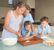 Τα παιδιά κάνουν το κέικ στην κουζίνα Στοκ Εικόνες