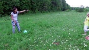 Τα παιδιά μαζί με τις μητέρες τους παίζουν με τη σφαίρα στο chamomile λιβάδι, κοντά στο δάσος έχουν τη διασκέδαση απόθεμα βίντεο