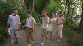 Τα παιδιά με την κάρτα περπατούν γύρω από την πόλη Κορίτσια στα όμορφα ελαφριά φορέματα απόθεμα βίντεο