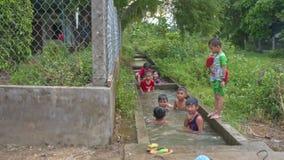 Τα παιδιά λούζουν στο κανάλι τομέων ρυζιού στο χωριό στο Βιετνάμ φιλμ μικρού μήκους